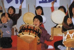 International coterie of kids bang happily on an array of drums