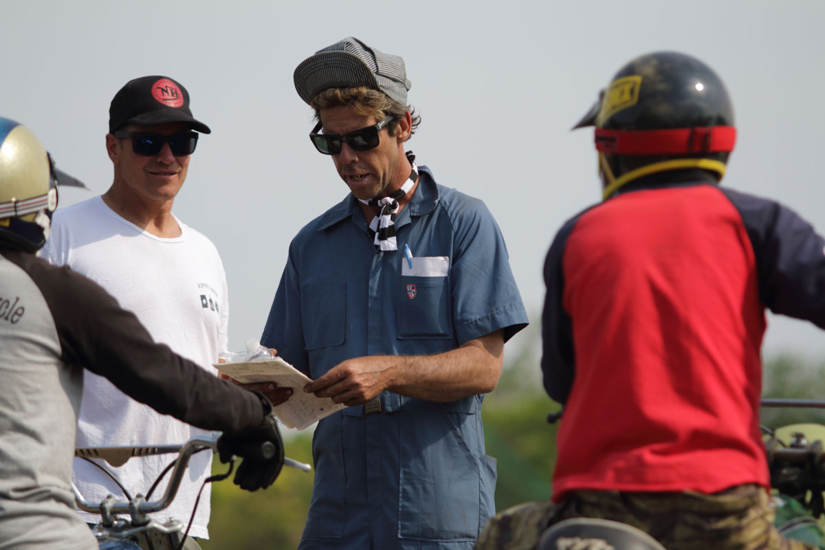 "Hell on Wheels' Meatball checks rider names while VonZipper founder Greg ""GT"" Tomlinson looks on"
