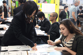 A student from Takata High teaches a Del Norte student the basics of writing kanji