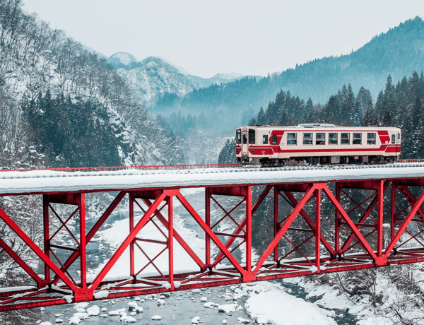 The Akita Nairiku Line passes over a red bridge during the winter