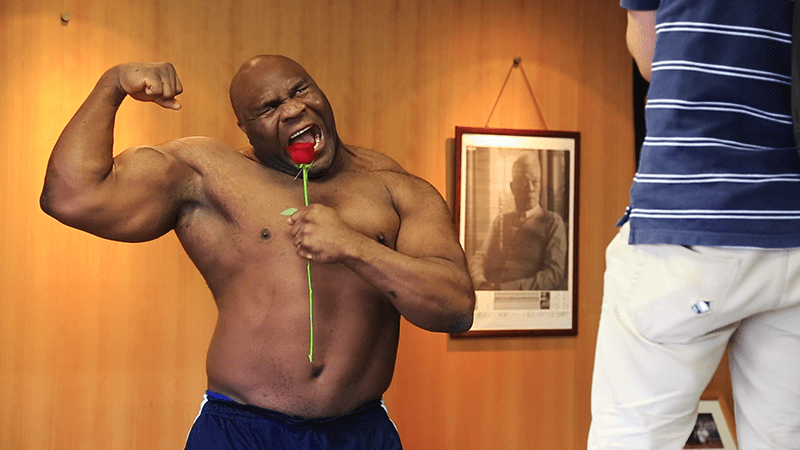 bob sapp posing with a rose and flexing his arm