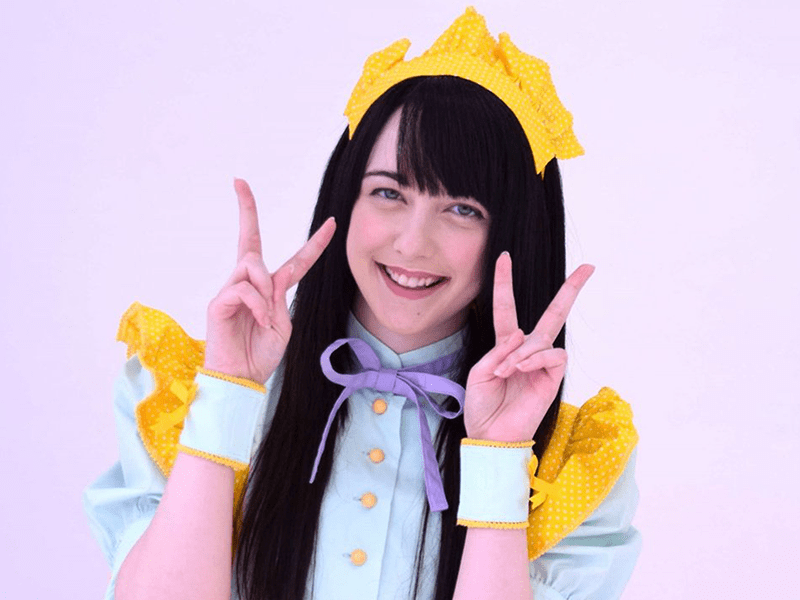 young woman wearing idol clothes and showing peace sign