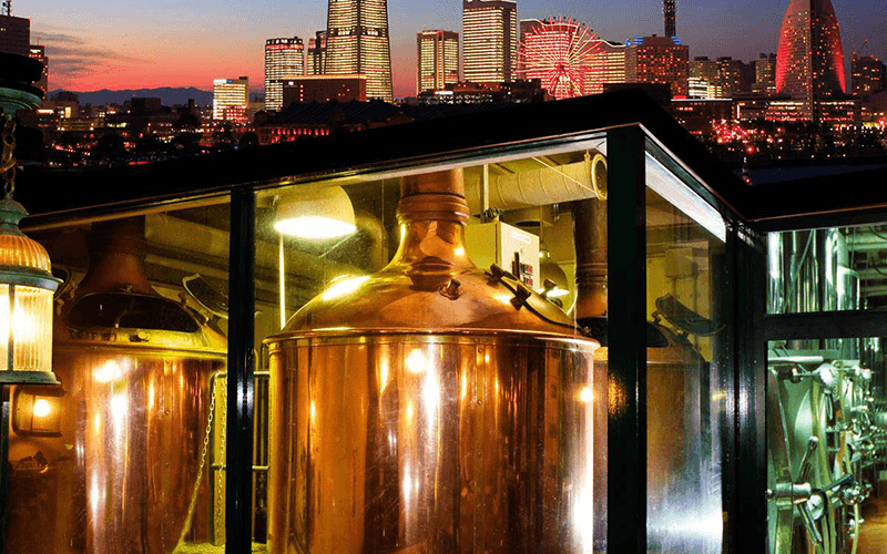 a night photograph of yokohama brewery with the yokohama skyline in the background