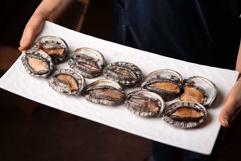 a person holding a plate of abalone which the Akita city of Happo is well known for
