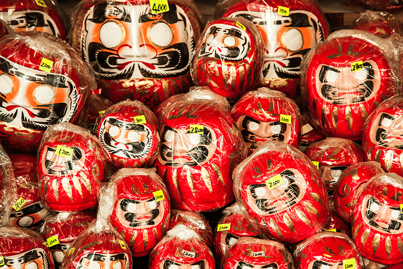 many daruma dolls stacked on top of each other