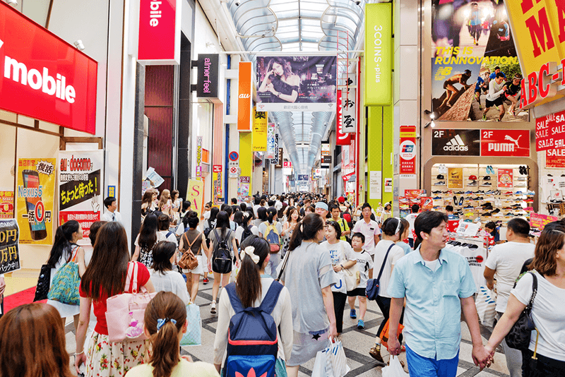 people walking on a busy shopping street in Japan