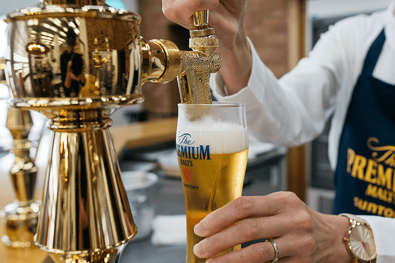 a server pouring a glass of suntory premium malts from a tap
