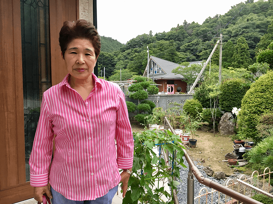 a woman from tohoku standing in front of her house
