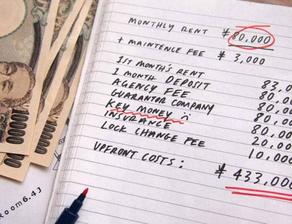 image of notebook calculating the costs of renting an apartment in Tokyo including key money, deposit etc, with pens and Japanese yen notes at the side.