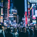 scene of a crowd in Shibuya Tokyo with neon signs