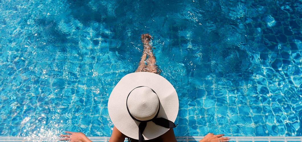 a woman sitting on the edge of an outdoor pool with a hat